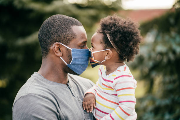 Father and toddler wearing mask outdoor stock photo