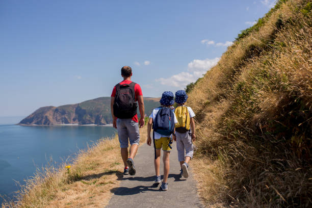 Padre y dos chicos, familias caminando por un pequeño sendero a lo largo de la impresionante costa de Devonshire cerca de Lynmouth en Devon - foto de stock