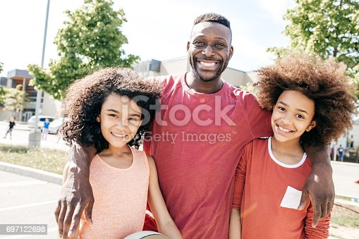 1082195070 istock photo Father and two  daughter as a basketball team 697122698