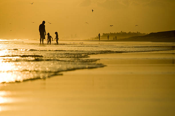 Father and two kids playing on the beach stock photo