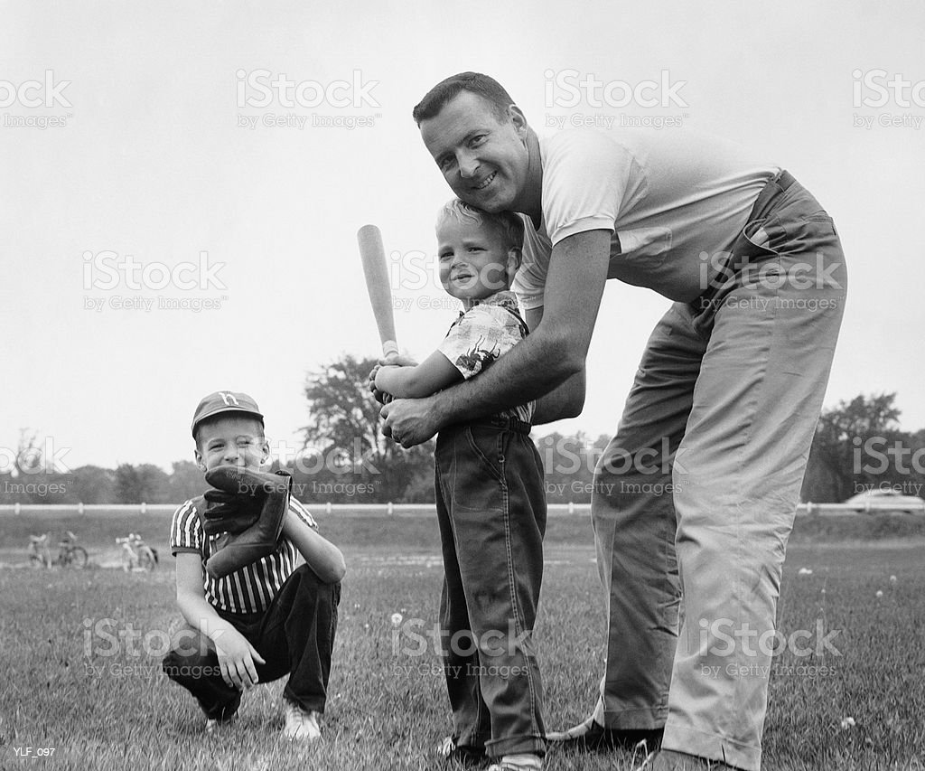Father and two sons playing baseball royalty-free stock photo