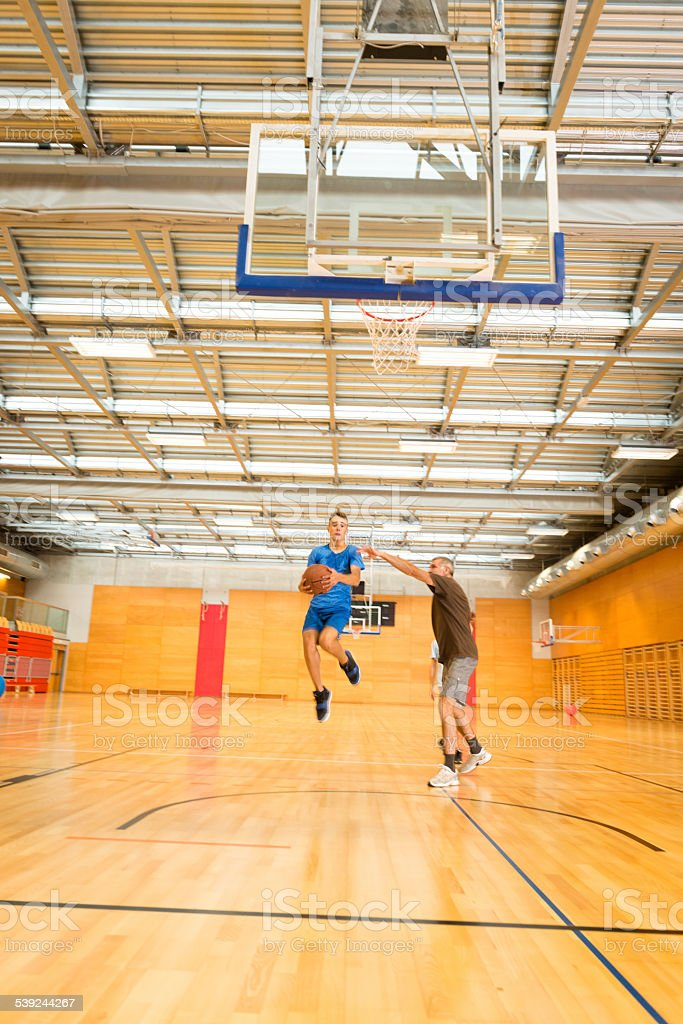 Father and Two Sons Playing Basketball, Sportshall, Europe royalty-free stock photo
