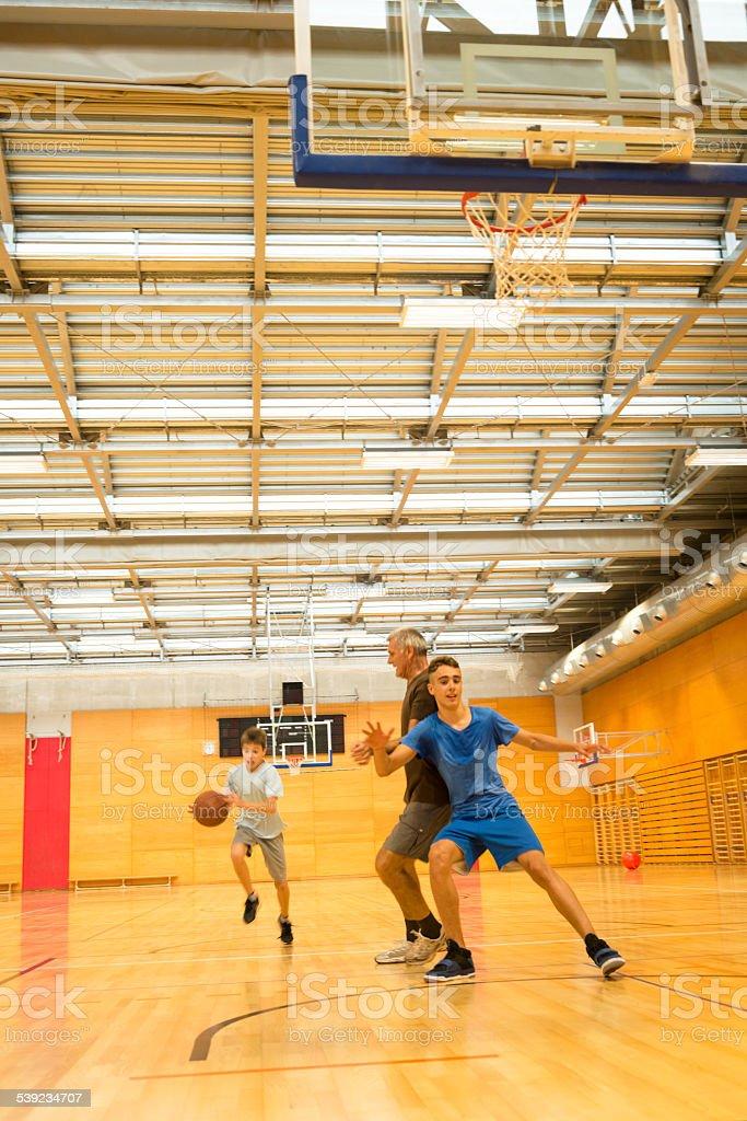 Padre y dos niños jugando al básquetbol, Sportshall, Eslovenia, Europa foto de stock libre de derechos