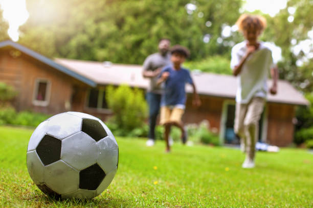 Father and two sons playing soccer at backyard of holiday villa stock photo