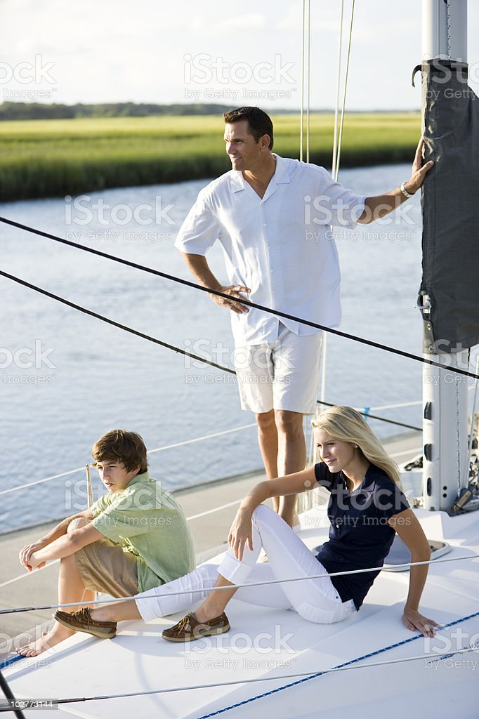 Father and two teenage children relaxing on boat royalty-free stock photo
