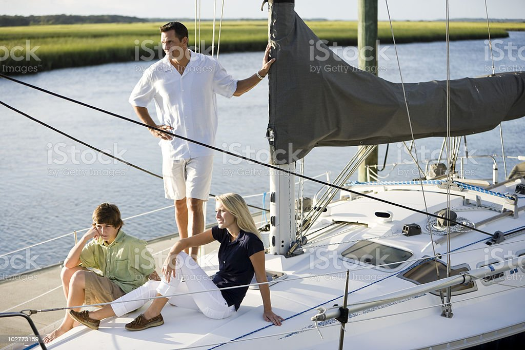 Father and two teenage children relaxing on boat stock photo
