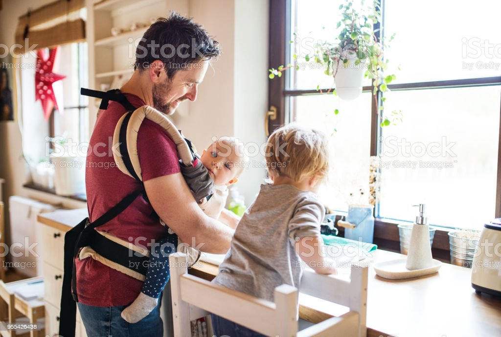 Father and two toddlers washing up the dishes. stock photo