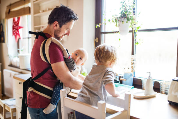 father and two toddlers washing up the dishes. - carrying stock pictures, royalty-free photos & images