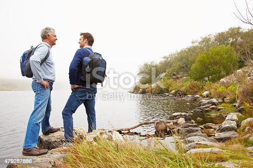istock Father and young adult son standing by a lake 479287886