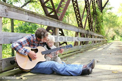 istock Father and Young Child Playing Guitar Outside at Park 475365352