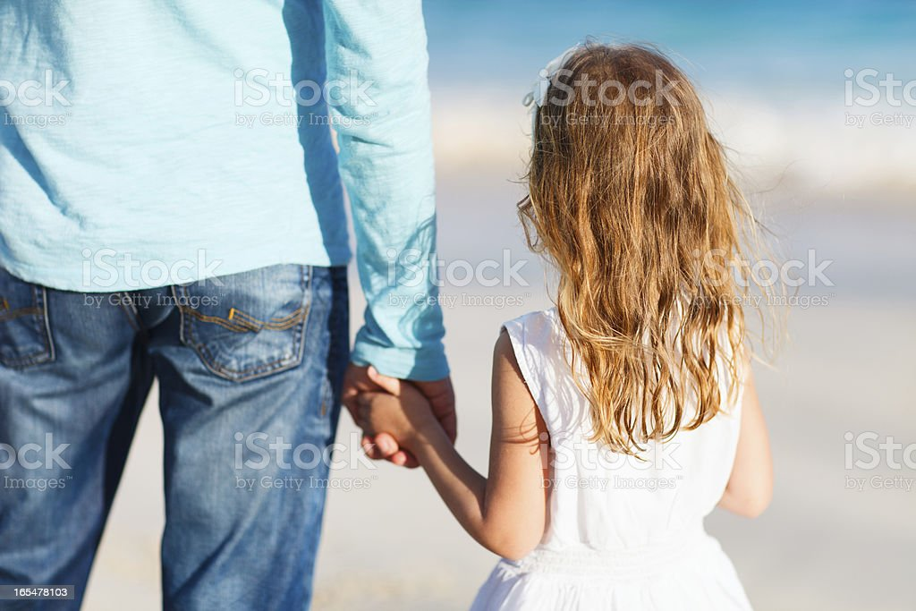 Father and young daughter holding hands outside stock photo