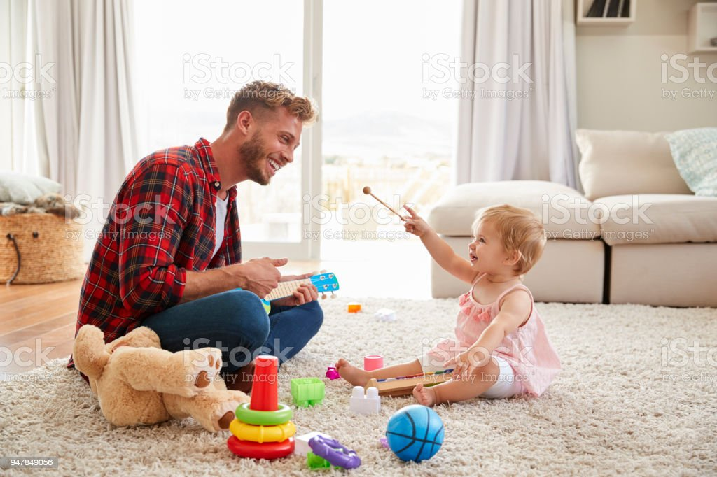 Father and young daughter playing toy instruments at home stock photo