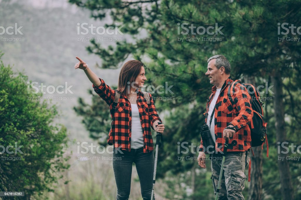 Father and young daughter trail hiking on mountain stock photo