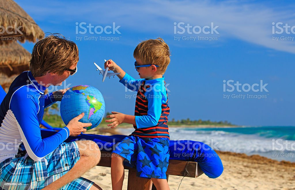 A father and young son playing with a globe on a beach father and son playing with globe and plane on the beach, travel concept 2015 Stock Photo