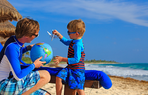 A Father And Young Son Playing With A Globe On A Beach Stock Photo - Download Image Now