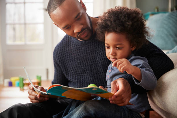 Father And Young Son Reading Book Together At Home stock photo