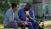 istock Father arguing teenage son sitting on campus bench, puberty age difficulties 1183419540