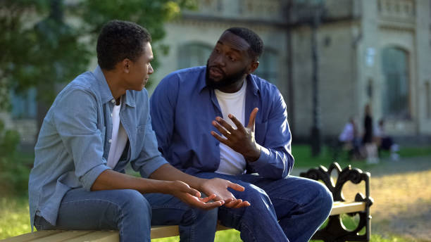 Father arguing teenage son sitting on campus bench, puberty age difficulties stock photo
