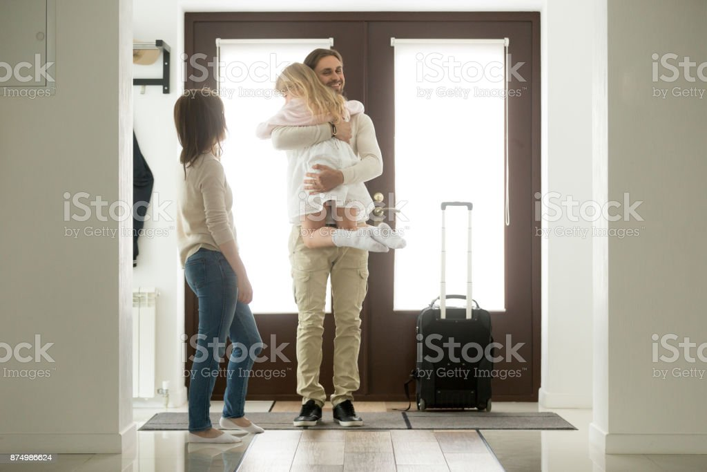 Father arrived came home returning after trip holding hugging daughter stock photo