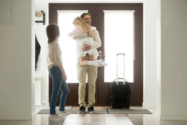 father arrived came home returning after trip holding hugging daughter - arrival stock photos and pictures