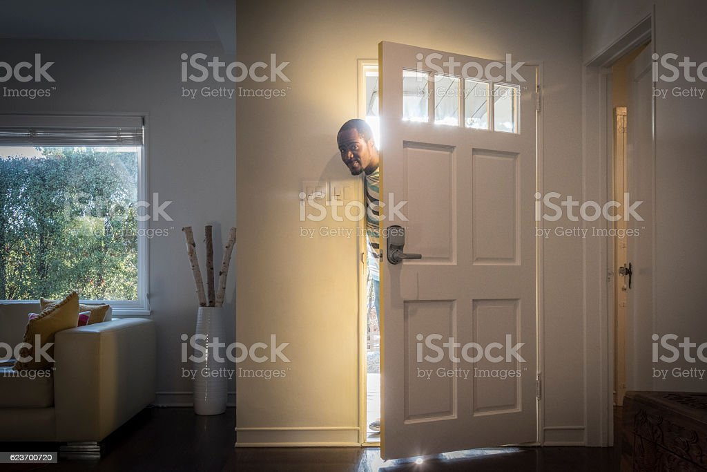 open front door. Father Arriving Home Peeping Through Open Front Door Stock Photo