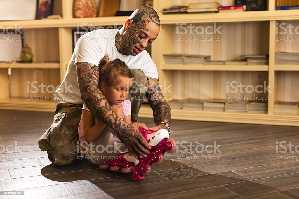 Father assisting his daughter with roller skates at home. stock photo