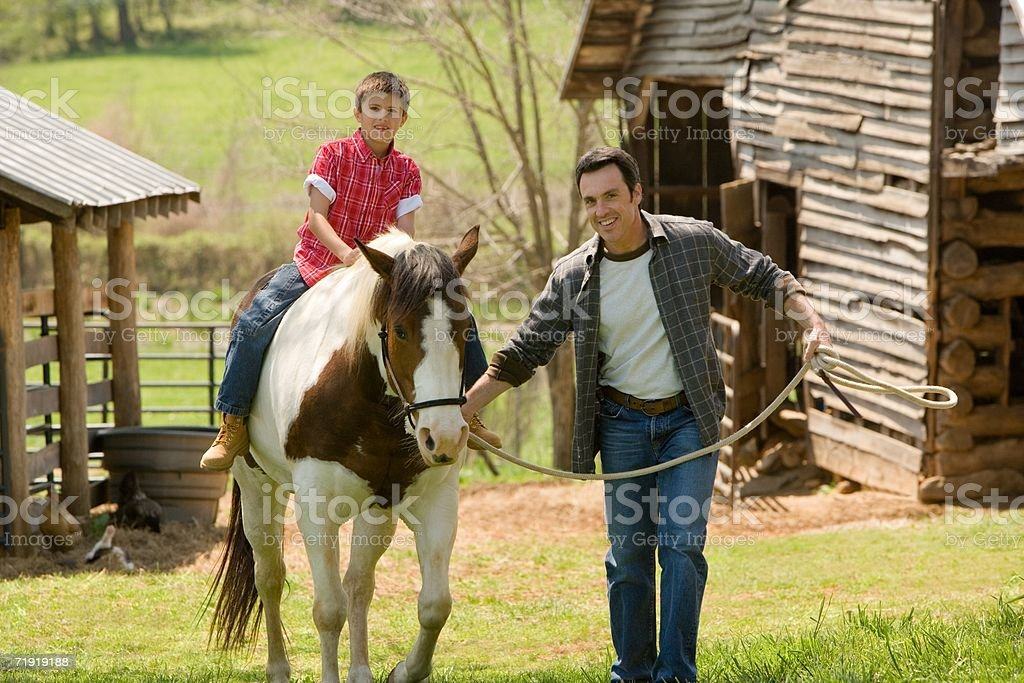 Father assisting son horseback riding royalty-free stock photo