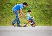 Father assisting his son in riding a tricycle