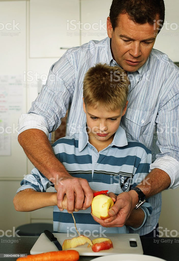 Father assisting son (10-12) peel apple royalty-free stock photo