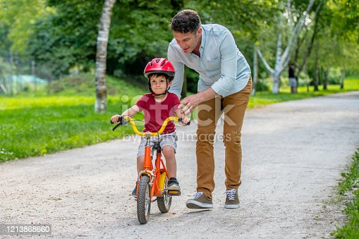Father helping his son learning to ride a bicycle in a public park.