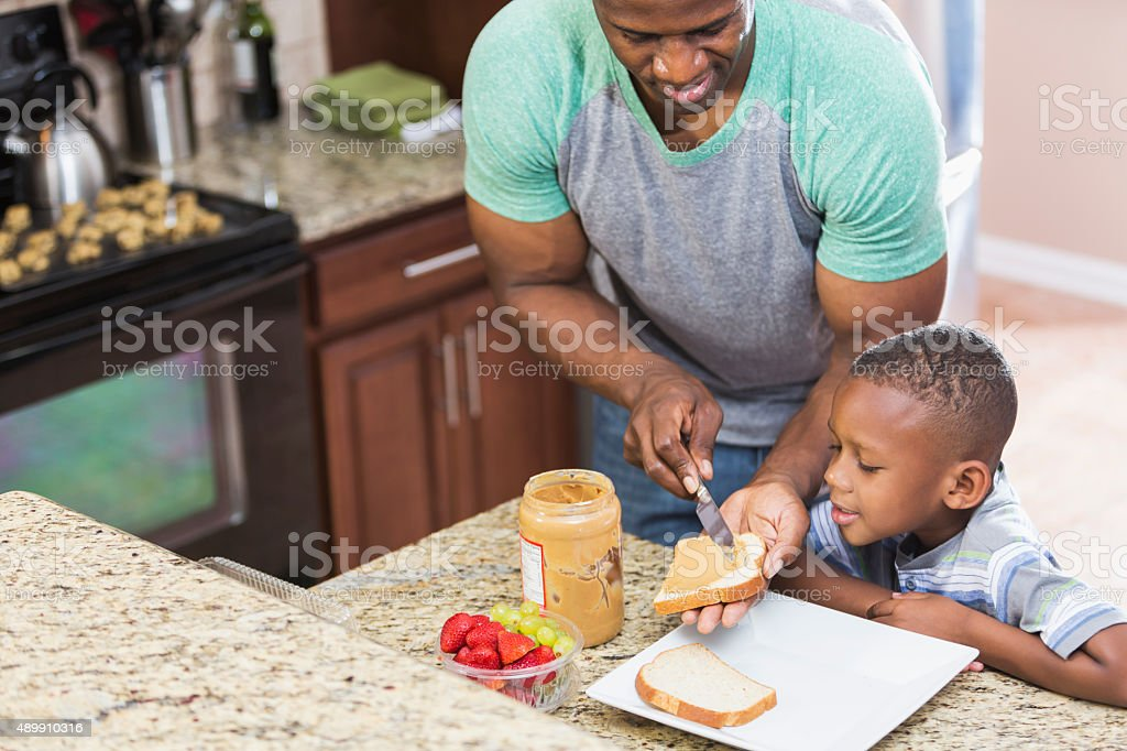 Father at home making peanut butter sandwich for son stock photo