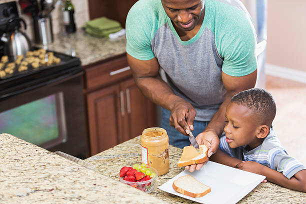 vater zu hause, erdnussbutter-sandwich für son - hausmannskost stock-fotos und bilder