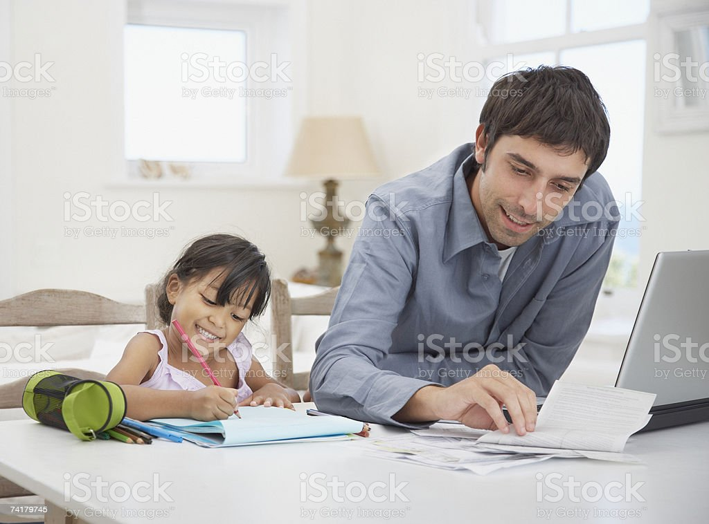 Father at laptop with daughter drawing royalty-free stock photo
