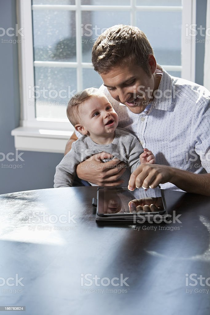 Father, baby and digital tablet stock photo