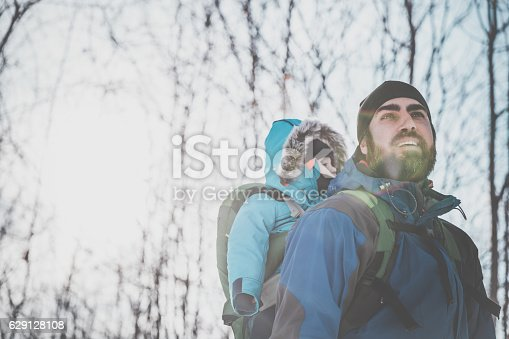 istock Father Backpacking Hiking with Baby in Winter Forest 629128108