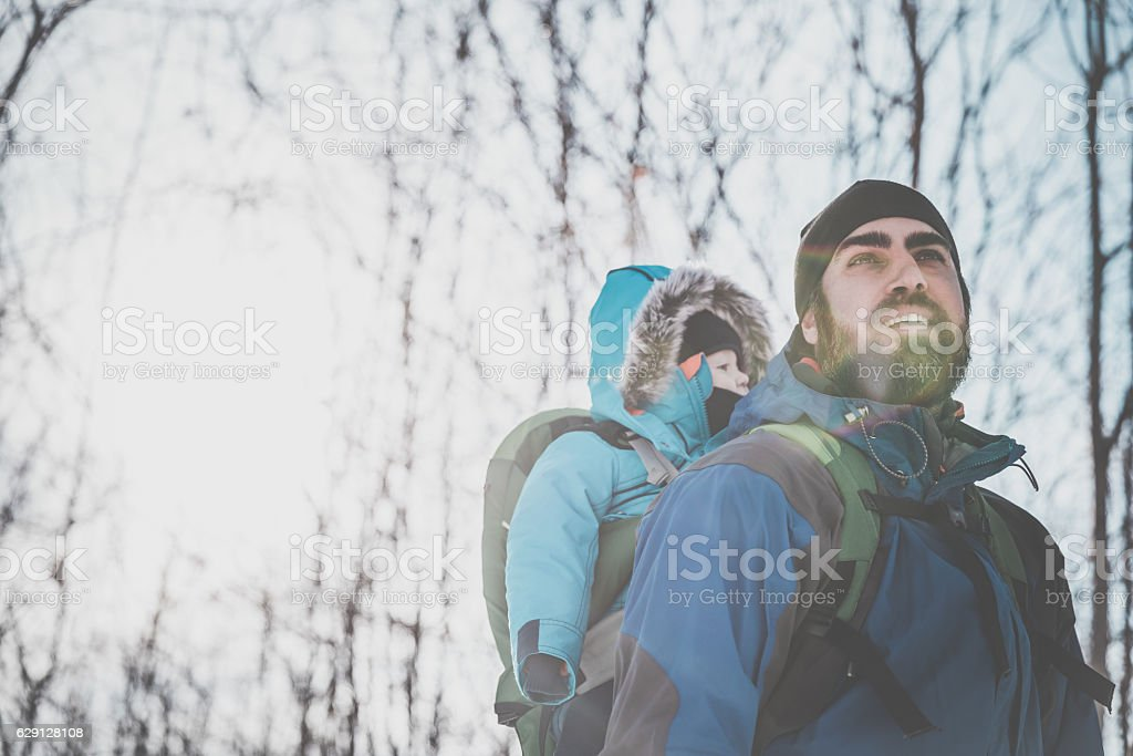 Father Backpacking Hiking with Baby in Winter Forest stock photo