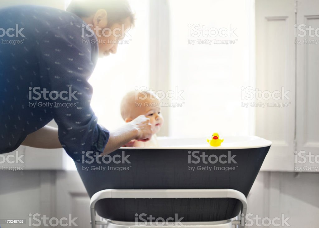 Father bathing baby stock photo