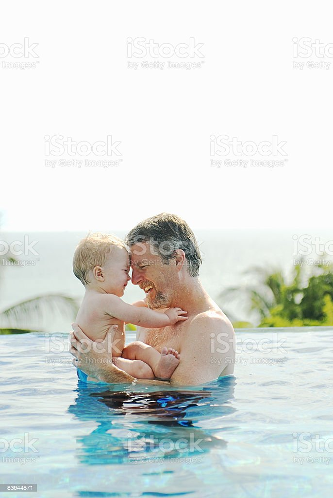 Father being affectionate with toddler son in pool Lizenzfreies stock-foto