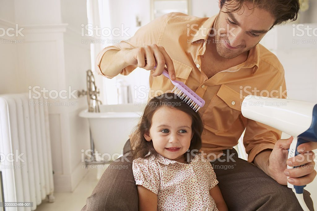 Father blowdrying daughter's (2-4) hair in bathroom, close-up stock photo