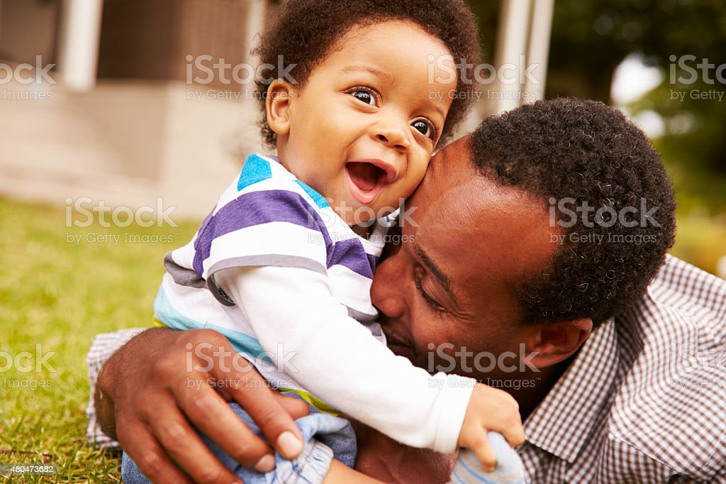 Father bonding with his toddler son in a garden stock photo