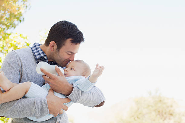 Father bottle feeding baby outdoors stock photo