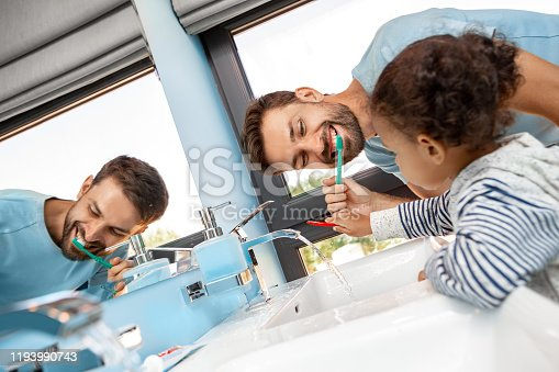 684029036 istock photo Father brushing teeth in bathroom with daughter 1193990743