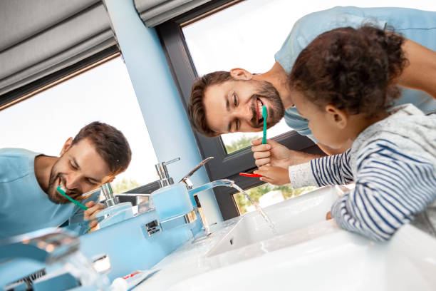 Father brushing teeth in bathroom with daughter stock photo