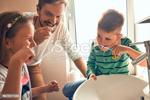 185211538istockphoto father brushing teeth with his kids 862931536