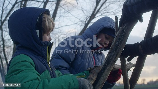 istock Father building teepee with sons. Riverside in the city 1132767517