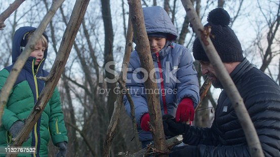 istock Father building teepee with sons. Riverside in the city 1132767532