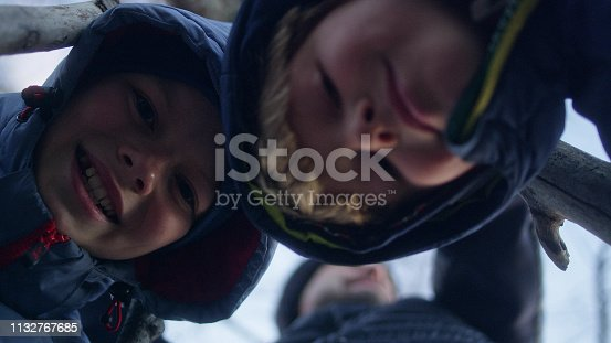 istock Father building teepee with sons. Riverside in the city 1132767685