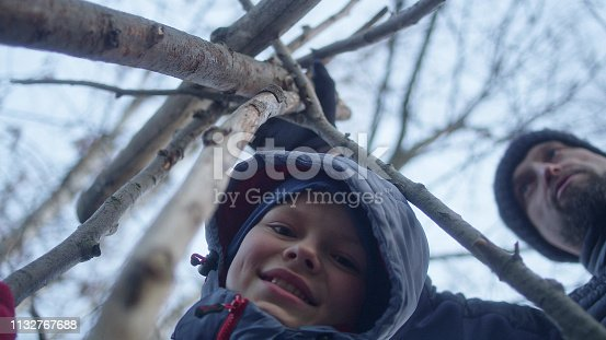 istock Father building teepee with sons. Riverside in the city 1132767688