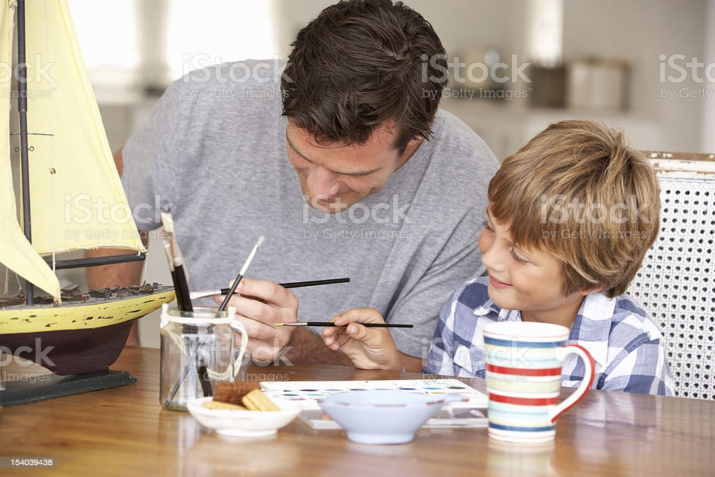 Father builds model ship with child stock photo