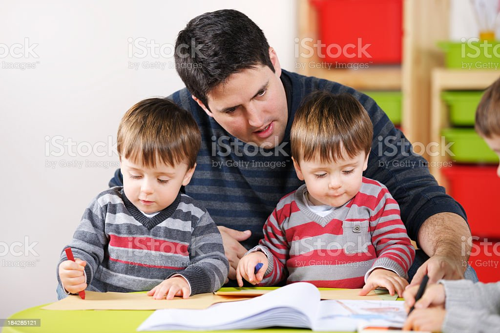 Father/ Carer Enjoying Doing Artwork With Sons royalty-free stock photo